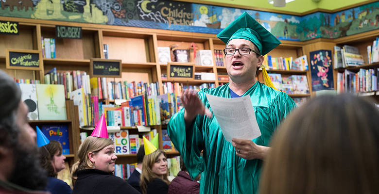 Kevin Smokler Speaking Wearing a Cap and Gown.